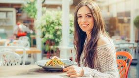 享用食物的少妇在餐馆,有她的午餐brea 免版税图库摄影