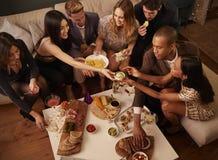 享用饮料和快餐的小组朋友在党 免版税库存图片