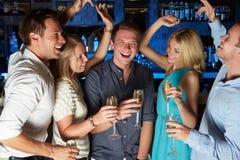 享用香宾的玻璃在酒吧的小组朋友 库存图片