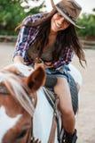 享用骑乘马的快乐的妇女女牛仔在村庄 图库摄影