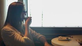 享用鲜美咖啡的美丽的少妇考虑生活在餐馆 免版税库存照片