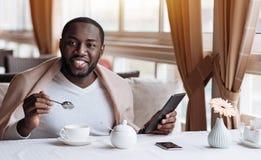 享用他的在咖啡馆的正面非裔美国人的人早餐 免版税库存图片