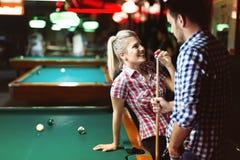 享用年轻的夫妇演奏落袋撞球在日期 库存照片