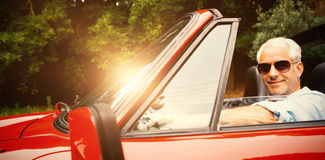 享用他的红色敞篷车的英俊的人 免版税图库摄影