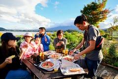 享用他们的薄饼和啤酒的亚裔访客 免版税库存照片