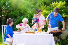 享用bbq格栅的大愉快的家庭在庭院里 免版税库存照片