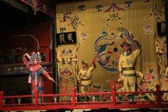 京剧,人跳舞在阶段的战斗与明亮的传统衣裳的一个女性战士 免版税库存图片