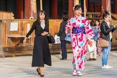 京都,日本- 2017年11月7日:一件五颜六色的和服的一个女孩在城市街道上 复制文本的空间 免版税库存图片