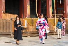 京都,日本- 2017年11月7日:一件五颜六色的和服的一个女孩在城市街道上 复制文本的空间 免版税库存照片