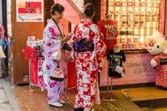 京都,日本- 2017年11月7日:一件和服的两个女孩在城市街道上 复制文本的空间 库存图片
