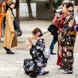 京都,日本- 2017年11月7日:一件和服的女孩在城市街道上 复制文本的空间 库存图片