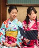 京都,日本- 2017年11月7日:两个日本女孩画象一件和服的在城市街道上 特写镜头 库存照片