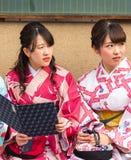 京都,日本- 2017年11月7日:两个日本女孩画象一件和服的在城市街道上 特写镜头 图库摄影