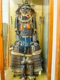 京都,日本- 2017年7月05日:关闭与盔甲、盾和保护的一套战士衣服,在的一个寺庙里面 库存照片