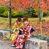 京都,日本- 2017年11月7日:和服的两个女孩坐一条长凳在城市公园 复制文本的空间 库存照片
