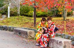 京都,日本- 2017年11月7日:和服的两个女孩坐一条长凳在城市公园 复制文本的空间 免版税库存图片