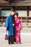 京都,日本- 2017年11月7日:在一件和服的一对爱恋的夫妇在镇中心 垂直 复制文本的空间 免版税库存图片