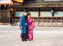 京都,日本- 2017年11月7日:在一件和服的一对爱恋的夫妇在镇中心 复制文本的空间 库存图片
