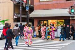 京都,日本- 2017年11月7日:小组一件和服的女孩在城市街道上 复制文本的空间 免版税库存图片