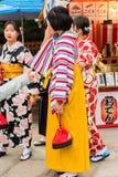 京都,日本- 2017年11月7日:小组一件明亮的和服的女孩在城市街道上 特写镜头 垂直 库存图片