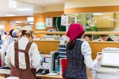 京都,日本- 2017年11月7日:工作者在一个地方咖啡馆的售票处 复制文本的空间 免版税库存照片