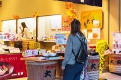 京都,日本- 2017年11月7日:有一个背包的一个女孩在日本商店 复制文本的空间 回到视图 库存照片