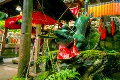 京都,日本- 2017年7月05日:与竹子的未认出的石雕象动物在他的在Fushimi Inari寺庙的嘴 免版税图库摄影