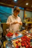 京都,日本- 2017年7月05日:举行在一个煮沸的微小的章鱼卖在西龟市场上的她的手上的未认出的妇女 免版税库存照片