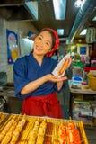 京都,日本- 2017年7月05日:举行在她的手上brochette的未认出的微笑的妇女,被卖在西龟市场上  库存照片