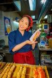 京都,日本- 2017年7月05日:举行在她的手上brochette的未认出的微笑的妇女,被卖在西龟市场上  免版税库存图片