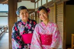 京都,日本- 2017年7月05日:关闭摆在为照相机的两个美丽的Japanesse女孩在Tenryu籍的Hojo霍尔  免版税库存照片