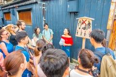京都,日本- 2017年7月05日:听在旅游女孩的人人群忠告和推荐对参观在 免版税图库摄影