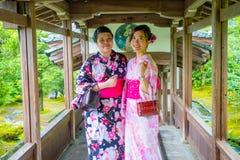 京都,日本- 2017年7月05日:摆在为照相机的两个美丽的Japanesse女孩在Tenryu籍的Hojo霍尔Arashiyama的 库存图片