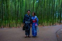 京都,日本- 2017年7月05日:摆在道路的照相机的未认出的夫妇在美丽的竹森林在Arashiyama 免版税库存图片