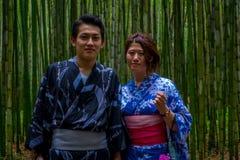 京都,日本- 2017年7月05日:摆在道路的照相机的未认出的夫妇在美丽的竹森林在Arashiyama 库存照片