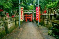 京都,日本- 2017年7月05日:有狐狸石头雕象的扔石头的道路在Fushimi Inari寺庙Fushimi Inari的每边 免版税库存图片