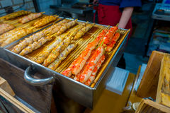 京都,日本- 2017年7月05日:烤食物在西龟市场上,是位于中心的一条室内购物街道  免版税库存照片