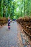 京都,日本- 2017年7月05日:走在道路的未认出的妇女在美丽的竹森林在Arashiyama,京都 库存照片