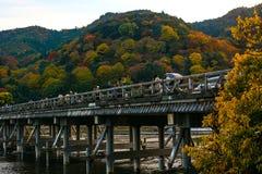 京都,日本- 2016年11月18日-享受秋天的颜色沿Togetsu桥梁的游人在京都` s Arashiyama地区duri 库存图片