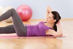 亭亭玉立的中间妇女做她的健身锻炼 免版税库存图片