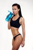 亭亭玉立的健身妇女饮用水正面图  免版税库存图片