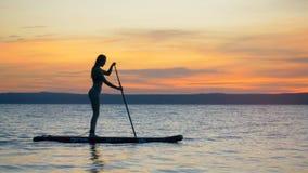 亭亭玉立的可爱的妇女继续前进她的横跨日落水的paddleboard 影视素材