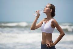 年轻亭亭玉立的在训练的妇女饮用水在海滩以后 免版税图库摄影