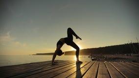 亭亭玉立的在轮子姿势的女孩实践的瑜伽剪影在日落的河码头 股票视频