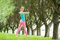 年轻亭亭玉立的夫人训练在公园 免版税图库摄影