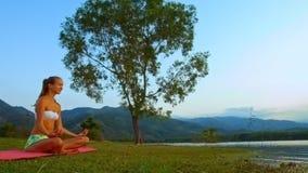 亭亭玉立的女孩在姿势莲花休息由奇怪的孤立树在小山 股票录像