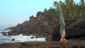 亭亭玉立的女孩在岩石沿海慢动作的sirsasana站立 影视素材