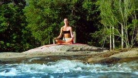 亭亭玉立的女孩在瑜伽姿势莲花思考由有急流的河 影视素材