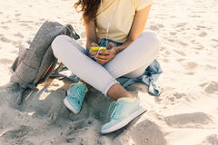 年轻亭亭玉立的女孩坐在牛仔裤和黄色T石牌的海滩 库存图片