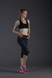亭亭玉立的女性的身体做在灰色低调,完善的金发碧眼的女人的activewear的posin 库存图片